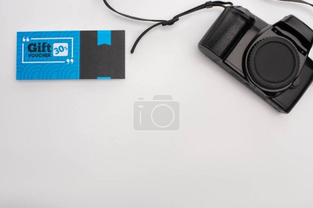Top view of gift voucher near digital camera on white surface with copy space