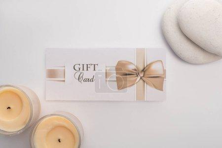 Photo pour Vue du dessus de la carte cadeau près des bougies et des pierres zen sur fond blanc - image libre de droit