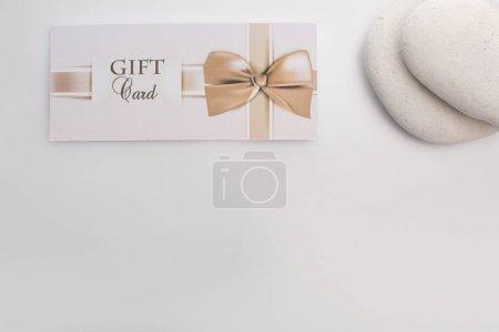 Photo pour Vue du dessus de la carte cadeau près de pierres zen sur fond blanc - image libre de droit