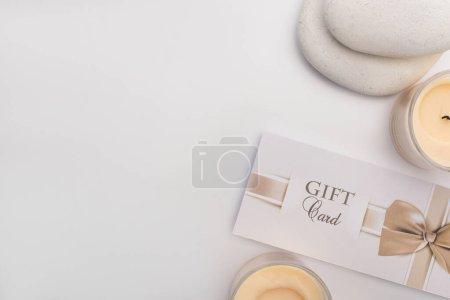 Photo pour Vue du dessus de la carte cadeau, des pierres zen et des bougies sur fond blanc - image libre de droit