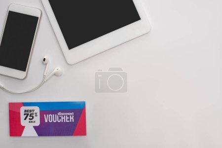 Top view of gadgets and earphones near discount voucher on white background