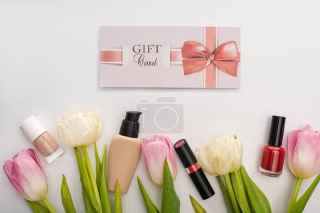 Photo for Top view of gift card near decorative cosmetics and flowers on white surface - Royalty Free Image