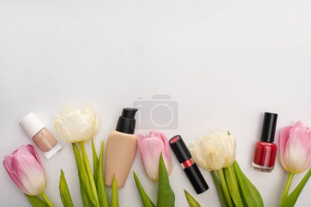 Top view of tulips with leaves and decorative cosmetics on white background