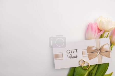 Photo for Top view of gift card, wedding rings and tulips on white background - Royalty Free Image
