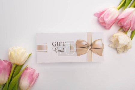 Photo pour Vue du dessus de la carte cadeau près des tulipes sur fond blanc - image libre de droit