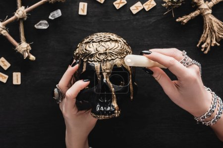 Photo for Cropped view of woman holding candle above skull near runes and crystals on black - Royalty Free Image