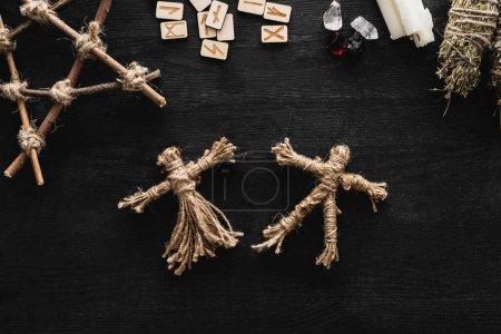 Photo pour Vue de dessus de poupées vaudou, runes scandinaves, pentagramme, bougies et cristaux sur noir - image libre de droit