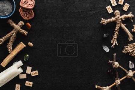 Photo pour Vue de dessus des poupées vaudou près du bol avec cendres, bougies, pierres et vieilles runes sur noir - image libre de droit