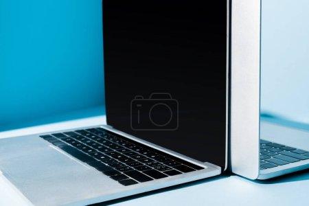 Photo pour Ordinateurs portables ouverts modernes avec écran blanc sur le lieu de travail bleu - image libre de droit