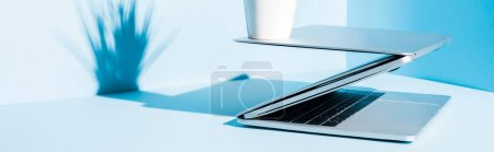 Photo for Modern laptops on blue workplace with plant , panoramic shot - Royalty Free Image