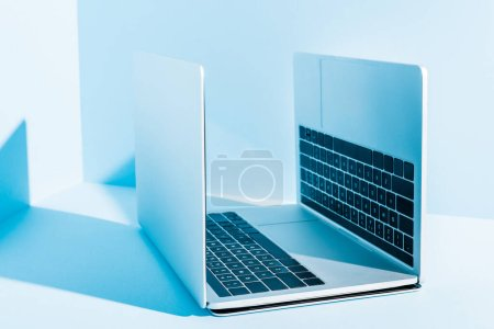 Photo for Modern laptops on blue workplace in sunlight - Royalty Free Image