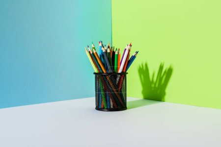 Photo pour Porte-crayons avec crayons de couleur sur fond bleu, vert et blanc - image libre de droit