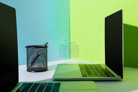 Photo pour Stylo dans le support près des ordinateurs portables modernes sur fond bleu, blanc et vert - image libre de droit