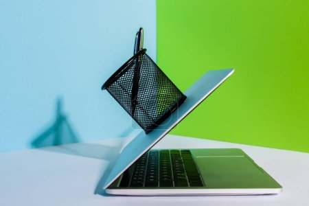 pen in holder on modern laptop on blue, white and green background