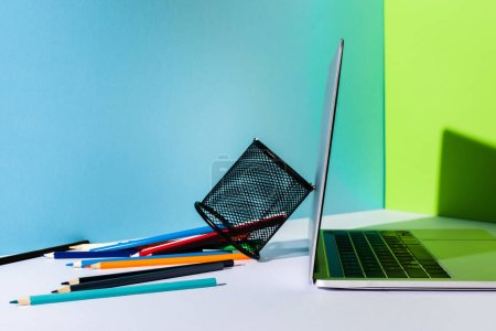 Photo for Scattered colored pencils from pencil holder near modern laptop on blue, green and white background - Royalty Free Image