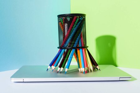 Photo for Colored pencils in pencil holder on modern laptop on blue, green and white background - Royalty Free Image