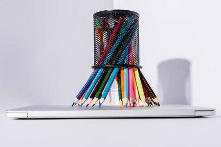 Photo pour Crayons de couleur dans le porte-crayon sur ordinateur portable moderne sur fond blanc - image libre de droit