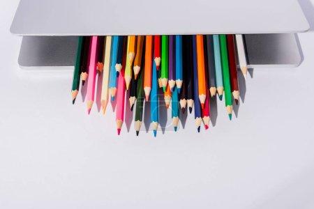 Photo pour Crayons de couleur dans un ordinateur portable moderne sur fond blanc - image libre de droit