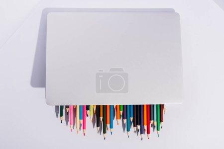 Photo pour Vue de dessus des crayons de couleur dans l'ordinateur portable moderne sur fond blanc - image libre de droit