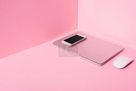 laptop, smartphone and computer mouse on pink background