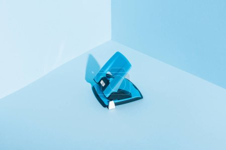 Photo for Blue plastic hole puncher on blue background - Royalty Free Image