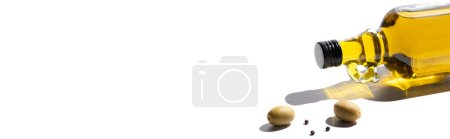 olive oil in bottle near green olives and black pepper on white background, panoramic orientation