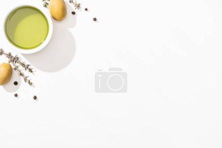 Ansicht von Olivenöl in Schüssel in der Nähe von grünen Oliven, Kräutern und schwarzem Pfeffer auf weißem Hintergrund