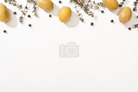 top view of green olives, herb and black pepper on white background