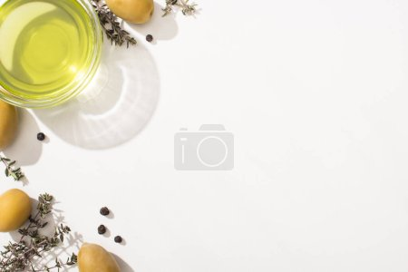top view of olive oil in glass bowl near green olives, herb and black pepper on white background