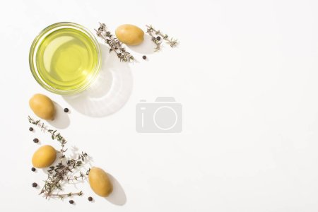 Photo for Top view of olive oil in glass bowl near green olives, herb and black pepper on white background - Royalty Free Image
