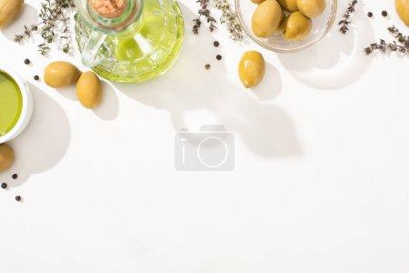 Ansicht von Olivenöl in Glasschale und Flasche in der Nähe von grünen Oliven, Kräutern und schwarzem Pfeffer auf weißem Hintergrund