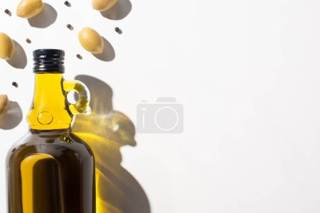 Photo for Top view of olive oil in bottle near green olives and black pepper on white background - Royalty Free Image