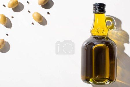 Photo pour Vue du dessus de l'huile d'olive en bouteille près des olives vertes et du poivre noir sur fond blanc - image libre de droit