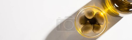 top view of olive oil in bottle near green olives in bowl in shadow on white background, panoramic orientation