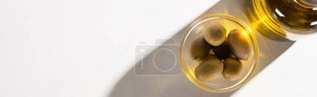Photo pour Vue du dessus de l'huile d'olive en bouteille près des olives vertes dans un bol à l'ombre sur fond blanc, orientation panoramique - image libre de droit