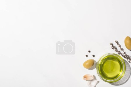 Photo for Top view of olive oil in bowl near green olives, garlic, herb and black pepper on white background - Royalty Free Image