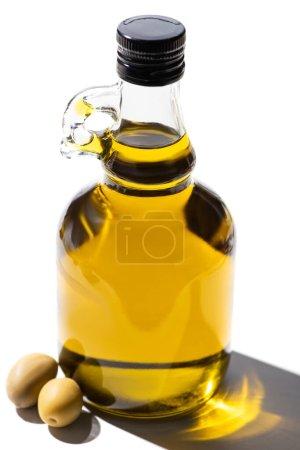 Photo pour Huile d'olive en bouteille près des olives vertes sur fond blanc - image libre de droit