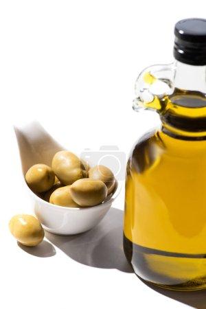 Photo pour Huile d'olive en bouteille près des olives vertes en bateau à sauce sur fond blanc - image libre de droit