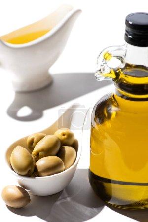 Photo pour Foyer sélectif de l'huile d'olive en bouteille et bateau à sauce près des olives vertes dans un bol sur fond blanc - image libre de droit