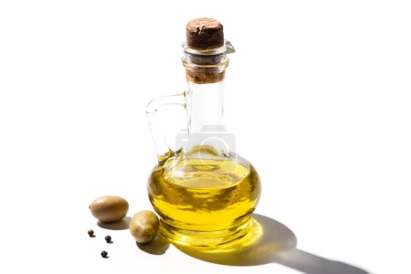 olive oil in jar near green olives and black pepper on white background