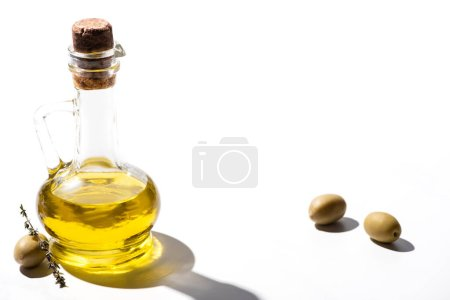 olive oil in jar near green olives with herb on white background