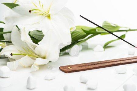 Photo pour Bâton d'arôme sur support en bois près des lis sur fond blanc - image libre de droit