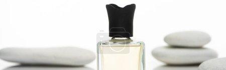 selektiver Fokus von Parfüm in der Flasche in der Nähe von Wellness-Steinen isoliert auf weißem Hintergrund, Panoramaaufnahme