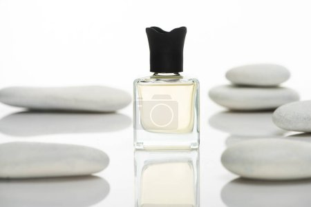 selective focus of home perfume in bottle near spa stones on white background