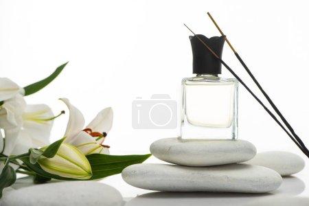Photo pour Bâtons d'arôme et de parfum sur des pierres de spa près de lis isolés sur blanc - image libre de droit