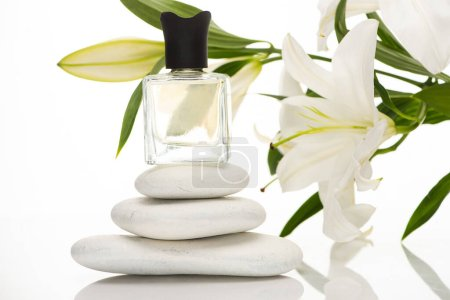 Photo for Home perfume in bottle near spa stones and lilies on white background - Royalty Free Image