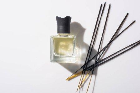 Photo pour Vue de dessus des bâtons d'arôme près du parfum en bouteille sur fond blanc - image libre de droit