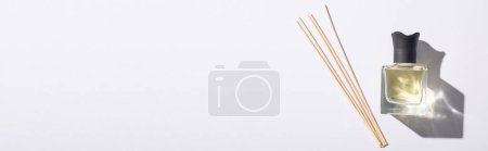 Photo for Top view of aroma sticks near perfume in bottle on white background, panoramic shot - Royalty Free Image