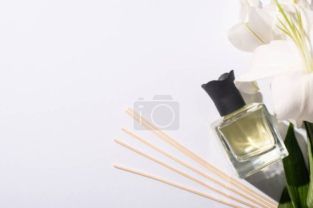 top view of aroma sticks with perfume in bottle near lilies on white background