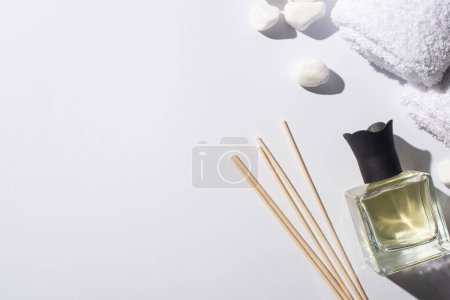 Photo pour Vue de dessus des bâtons d'arôme avec parfum en bouteille près de pierres de spa et serviette sur fond blanc - image libre de droit